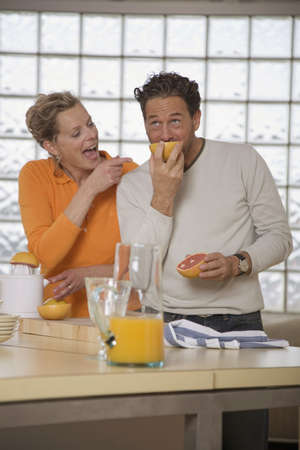 egoistic: Mature couple in kitchen, Man eating grapefruit LANG_EVOIMAGES