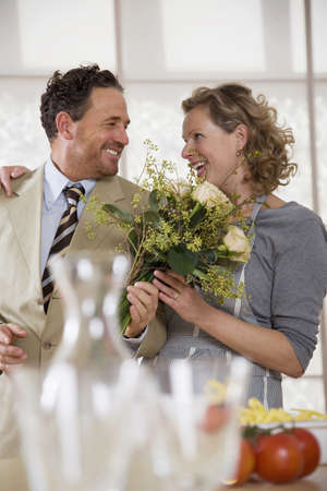 personable: Mature couple in kitchen with flower bouquet