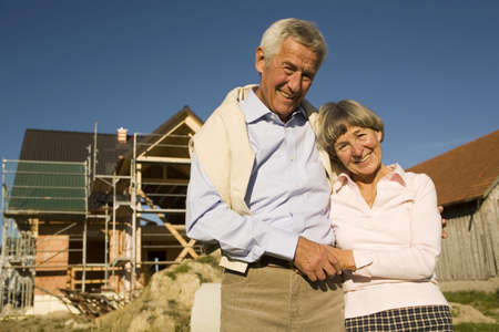70 year old man: Senior couple in front of partially built house LANG_EVOIMAGES
