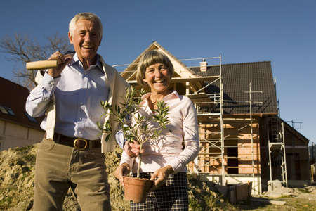 dark ages: Senior couple in front of partially built house LANG_EVOIMAGES