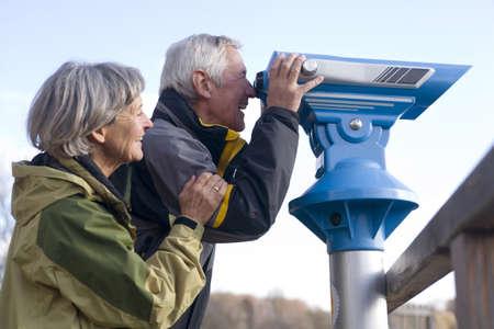 Senior couple, man looking through telescope, side view
