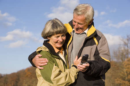 embracement: Senior couple, man holding mobile phone