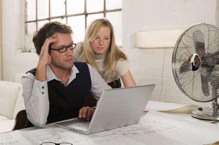 Young man and young woman working on laptop Stock Photo - 23853372