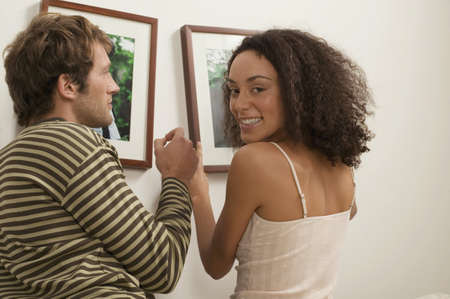 gratify: Young couple hanging up picture frame, woman smiling