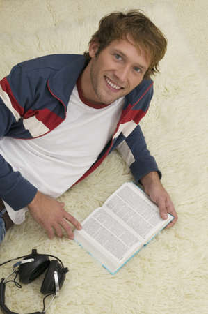 smile please: Young man lying on floor, reading book