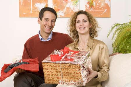 confiding: Couple sitting on sofa, holding Christmas presents
