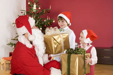 well behaved: Children (3-7) receiving presents from Santa, smiling LANG_EVOIMAGES