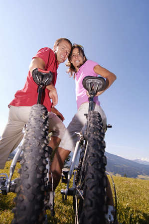 mountainbiking: Young couple on bicycle, smiling, low angle view, portrait