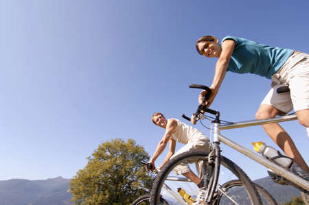 non moving activity: Young couple riding mountain bike, smiling, low angle view