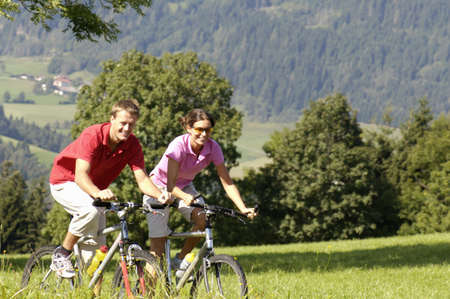 mountain bicycling: Young couple riding mountain bike on meadow, smiling