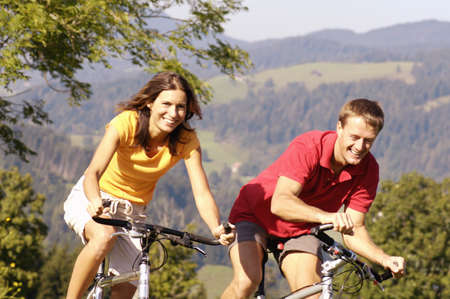 mountain bicycling: Young couple riding bicycle, smiling, mountains in background LANG_EVOIMAGES