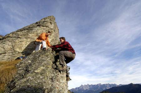 exert: Couple climbing on summit