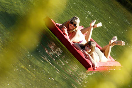 17 18 years: Two teenage girls (16-17) floating on air bed in lake, tilt view