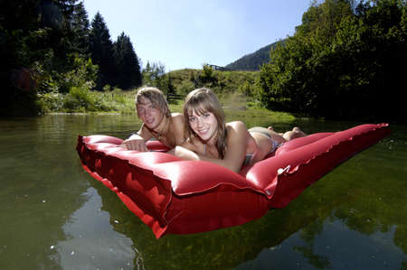 kind hearted: Teenage couple lying on air bed, smiling, portrait LANG_EVOIMAGES