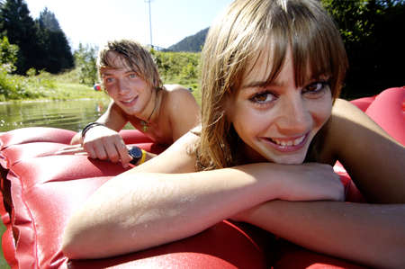kind hearted: Young couple lying on air bed, smiling, close-up