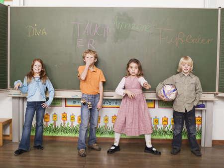 juxtaposing: Children (4-7) standing in front of blackboard, portrait LANG_EVOIMAGES