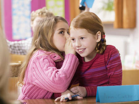 kindly: Girls (4-7) whispering in classroom