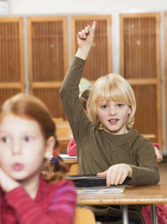 gratified: Boy (4-7) raising hand in classroom LANG_EVOIMAGES