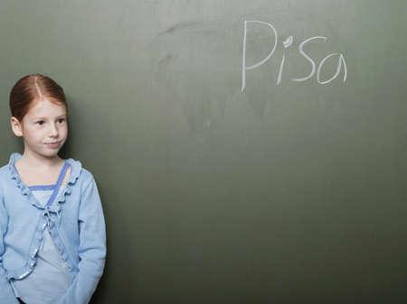 Girl (4-7) standing by blackboard, looking away