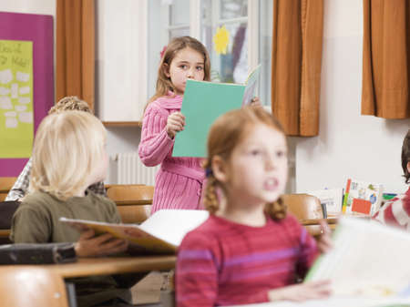 querying: Children (4-7) in classroom, focus on girl reading book in background