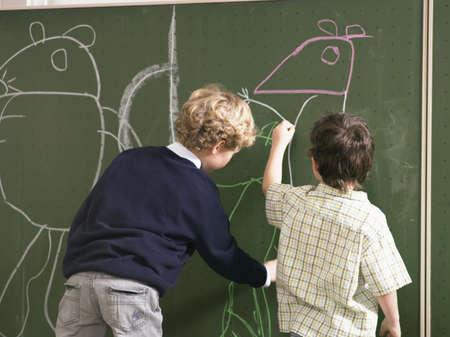 left handed: Boys (4-7) drawing on blackboard, rear view LANG_EVOIMAGES