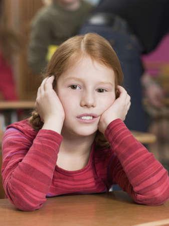 in low spirits: Girl leaning on school desk LANG_EVOIMAGES