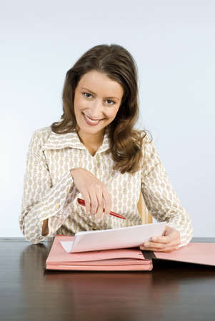mirthful: Young woman holding paper, smiling, portrait LANG_EVOIMAGES