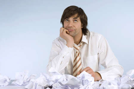 businessman pondering documents: Man sitting at desk with crumpled papers, looking upwards