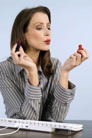 at resting: Businesswoman applying nail polish, blowing, close-up LANG_EVOIMAGES