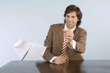 wasting away: Businessman throwing paper plane, smiling