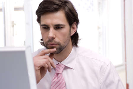 employe: Businessman using computer, hand on chin, close-up