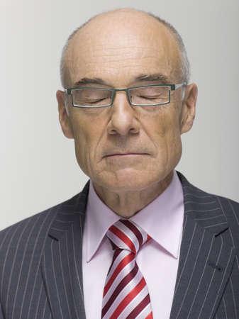 cogitate: Portrait of a Senior businessman eyes closed, close-up