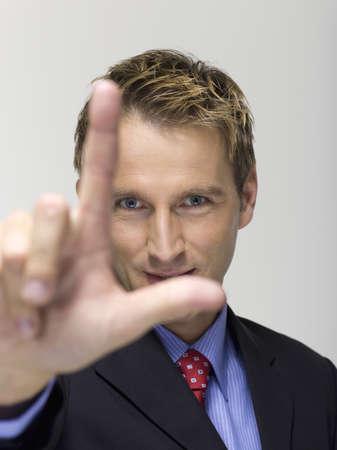 interiour shots: Young businessman showing two fingers, portrait LANG_EVOIMAGES