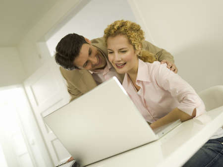 interiour shots: Young couple using laptop, smiling