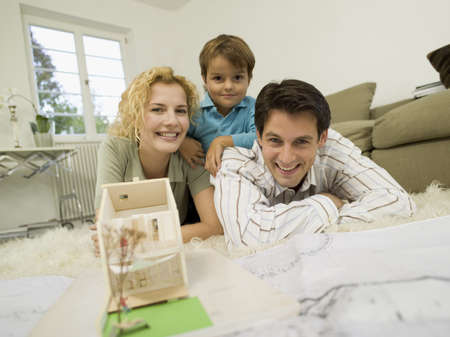 planned: Young family in living room, smiling, portrait