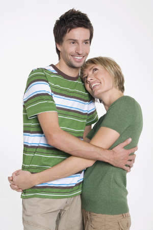 coherence: Front view portrait of young couple with arms around each other