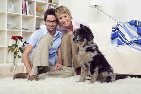 Couple in living room, with dog, portrait Stock Photo - 23853512