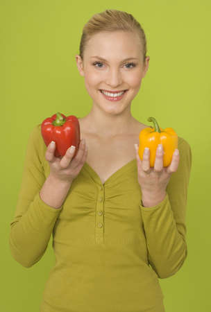 interiour shots: Young Woman Holding Red and yellow Bell Pepper, portrait