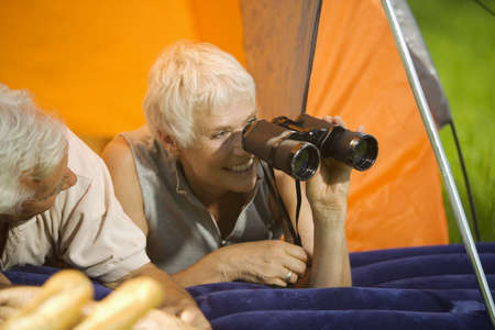 60 64 years: Senior couple camping, woman with field glasses, portrait