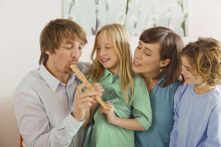 recorder: Family in living room, father playing recorder, portrait