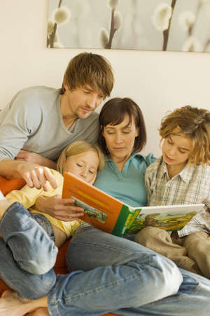 interiour shots: Family reading story book in living room