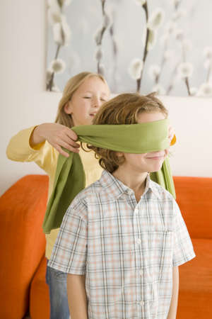 Boy (6-7) and girl (8-9) playing Blind Man's Bluff Stock Photo - 23890905