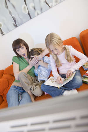 Mother and children watching television together Stock Photo - 23890907