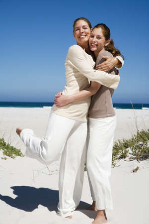 mirthful: Mother and daughter embracing on beach