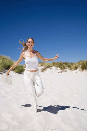 kind hearted: Woman running on beach LANG_EVOIMAGES