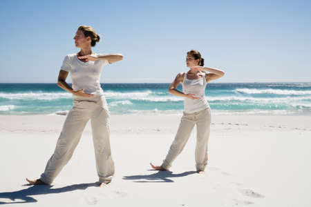 girls at the beach series: Two women exercising yoga on beach LANG_EVOIMAGES