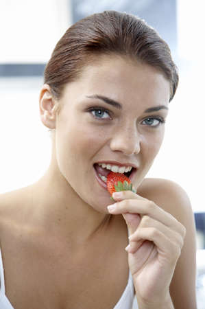 accrued: Young woman eatung strawberry