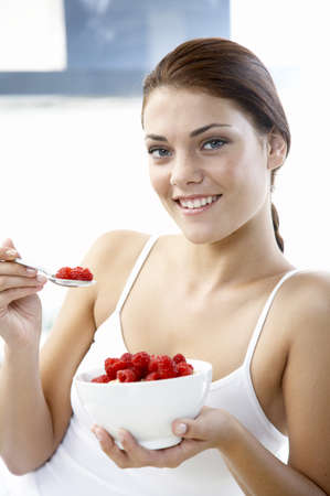 Young woman holding bowl with rasberries Stock Photo - 23890936