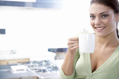 adulthood: Young woman in kitchen, holding cup