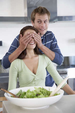 adulthood: Young couple in kitchen with salad bowl LANG_EVOIMAGES